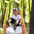 Baby goes down on child slides on the playground in the park — Stock Photo