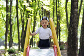 Calm baby climbs Children slide on the playground — Stock Photo