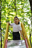 The kid climbed the slide on blurred background of trees — Stock Photo