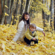 Happy mother and baby for a walk in the autumn park sat in the y — Stock Photo