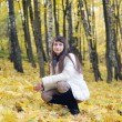 Young smiling woman rest in the autumn park — Stock Photo