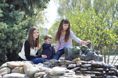 Beautiful girls and baby resting in the park near the fountain — Stock Photo