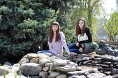 Beautiful girls resting in a park near the fountain — Stock Photo