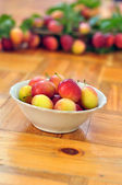 Plate of plums stands on wooden floor on blurred background — Stock Photo