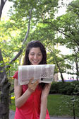 Girl reads newspaper — Stock Photo