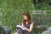 Girl writing in park — Stock Photo