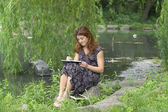 Girl writing in park — Stock Photo