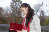 Girl reading Bible in park — Stock Photo