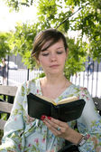 Girl outdoors with Bible — Stock Photo