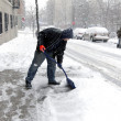 Stock Photo: Mshoveling during snow storm in New York