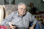 Senior man sitting on couch with headphone — Stok fotoğraf