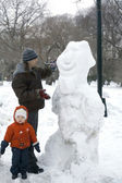 Father and child with snowman — Stock Photo