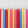 Thirty-two cylindrical candles colored lined — Stock Photo #26440123