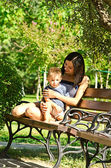 Mother with a son sit on a bench in a park — Stock Photo