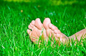 Womanish legs are in a green grass — Stock Photo