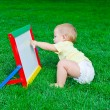 А beautiful little boy draws sitting on a lawn — 图库照片