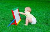 А beautiful little boy draws sitting on a lawn — Stock Photo
