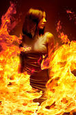 Young beautiful girl is in blazing flame — Stock Photo