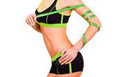 стройная фигура девушка находится в спортивная одежда с ленточкой сантиметр на руке — Стоковое фото