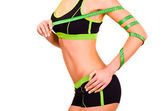 Slim figure of girl is in a sportwear with a centimetre ribbon on a hand — Foto Stock