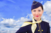 Beautiful young smiling stewardess on a background sky — Stock Photo