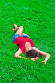 Young beautiful slim woman relaxing lying on the grass — Stock Photo