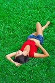 Vacker smal ung kvinna är avkopplande på gräsmattan — Stockfoto