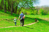 Father with his son and dog for a walk in the woods — Stock Photo