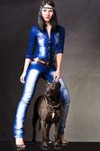 Mooie vrouw in jeans kleding permanent naast een hond — Stockfoto