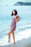 Young woman walking along the coast with shoes in hand — ストック写真