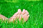 Piedi femminili in erba verde — Foto Stock