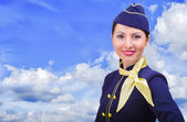 Beautiful smiling stewardess in uniform on a background sky — Stock Photo