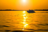 Silhouette of a boat floating in the sunset — Stock Photo