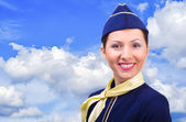 Beautiful smiling stewardess on a background sky — Stock Photo