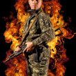 Soldier stands with a gun in his hand and safety glasses in a burning fire — ストック写真