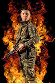 Soldier stands with a gun in his hand and safety glasses in a burning fire — Stock Photo