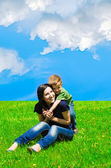 Young mother and son having fun in the meadow — Stock Photo