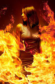 Portrait beautiful young woman is in blazing fire — Stock Photo