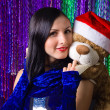 Christmas portrait of a beautiful young woman with teddy bear — Stock Photo #36463679