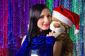 Christmas portrait of a beautiful young woman with teddy bear — Stock Photo