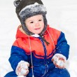 Portrait of little beautiful boy sitting on the snow — Stock Photo