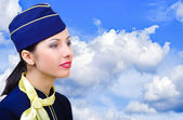 Portrait of a beautiful young stewardess in profile on the sky background — Stock Photo