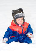 Portrait of beautiful boy sitting on the snow — Foto Stock