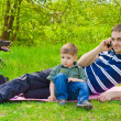 Man with son and dog outdoors talking on the phone — Stock Photo