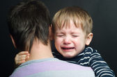 Crying child in the arms of his father — Stock Photo