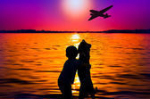 Silhouette of boy and dog at sunset watching aircraft — Stock Photo
