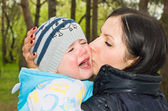 Portrait of a crying child in mother's arms — Stock Photo