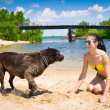 Young woman and dog playing on the beach — Stock Photo #48088365