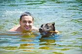 Man and dog floating — Stock Photo