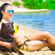 Beautiful young woman with a dog sitting on the beach — Stock Photo #48336727